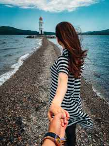 woman in stripes holding hands with person wearing bracelets